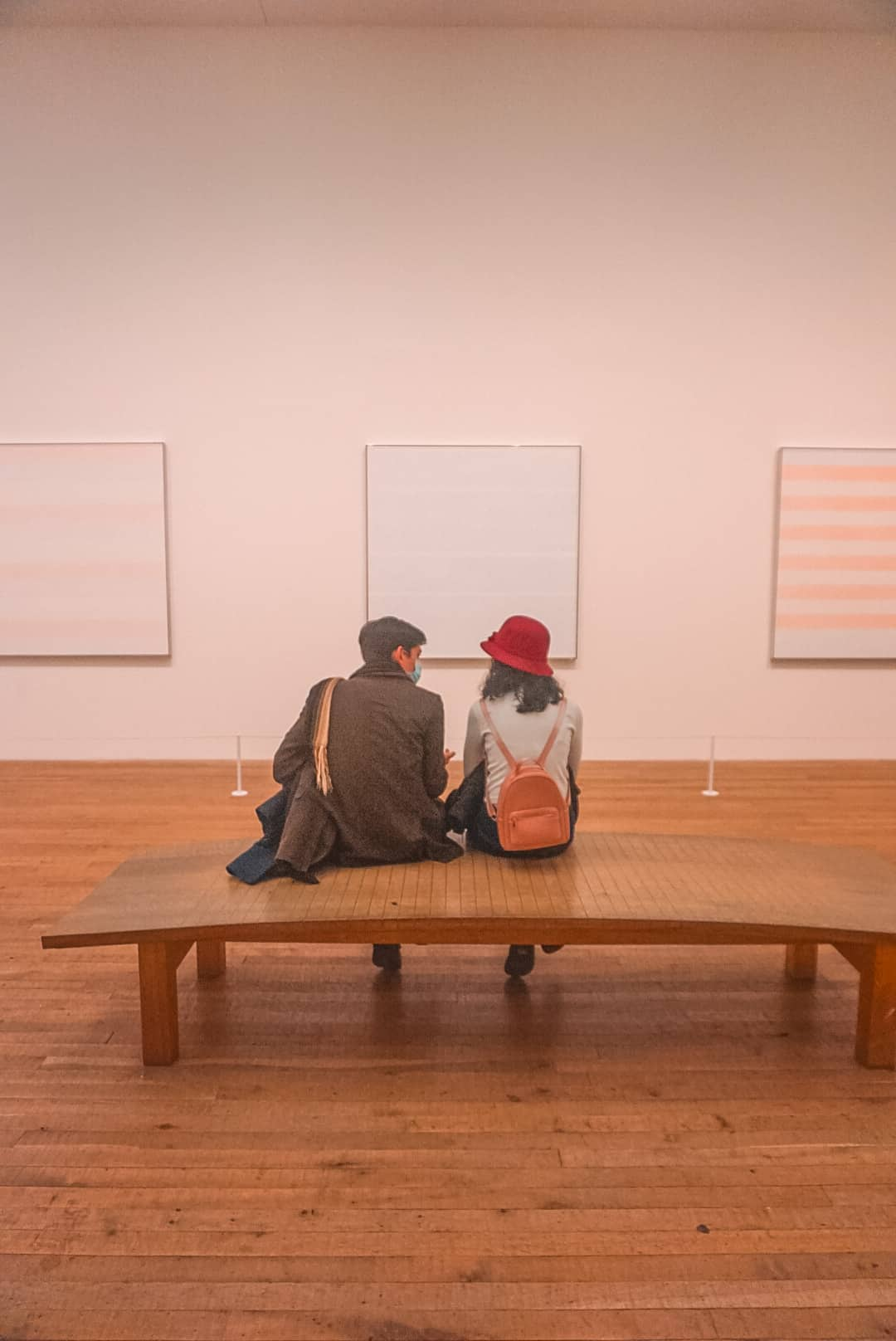 Couple-Sitting-Bench-In-Front-of-Modern-Art-in-London